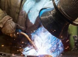 trabalhador realizando um processo de soldagema companhado de um equipamento de exaustão