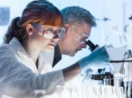 Uma mulher e um homem analisando amostras em um laboratório