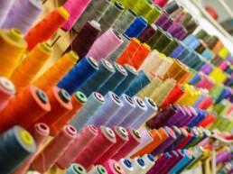 prateleira com linhas de costura de diversas cores
