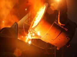 Grande tanque despejando metais derretidos em outra plataforma em um processo de fundição